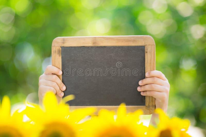 Placa do quadro-negro nas mãos imagens de stock royalty free