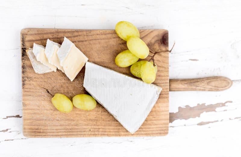 Placa do queijo Brie cremoso na placa de corte rústica sobre o wo branco foto de stock