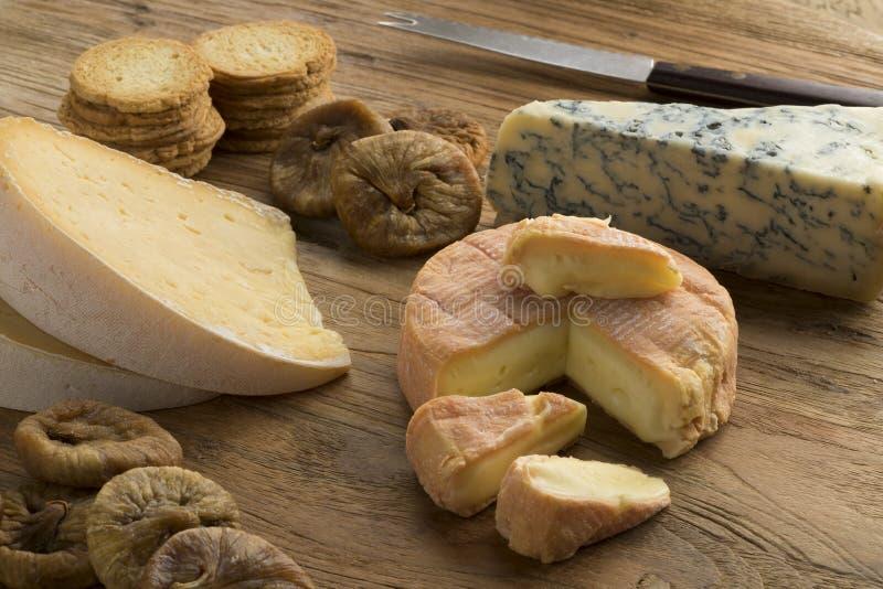 A placa do queijo com uma variedade de queijos fecha-se acima foto de stock