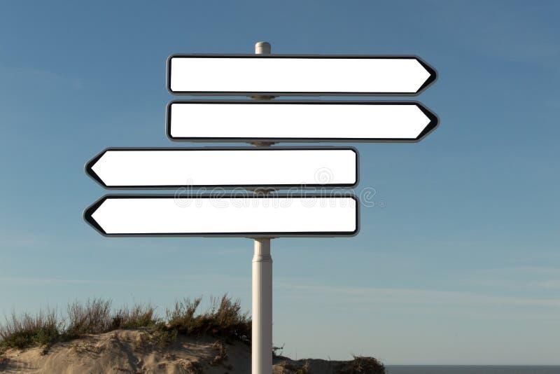 Placa do sentido da seta da estrada de quatro sinais vazia na rua fotografia de stock