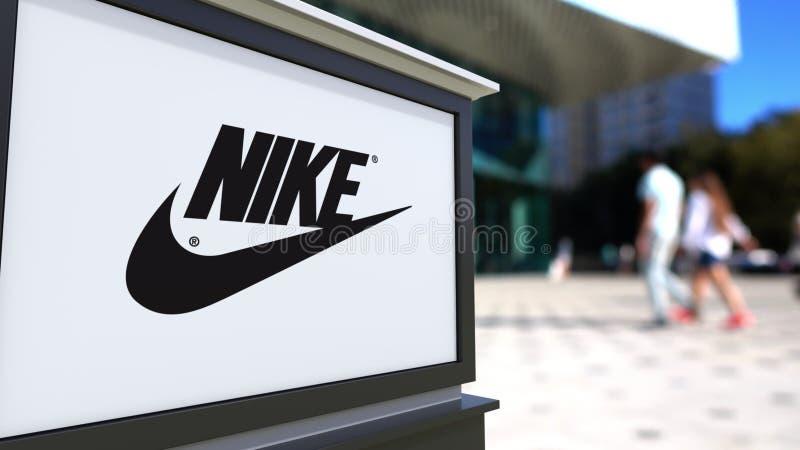 Placa do signage da rua com inscrição e logotipo de Nike Centro borrado do escritório, fundo de passeio dos povos 3D editorial ilustração stock