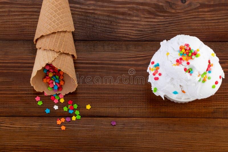 A placa do swith da colher do gelado de baunilha cones polvilha e da waffle no fundo de madeira com espa?o da c?pia fotografia de stock royalty free