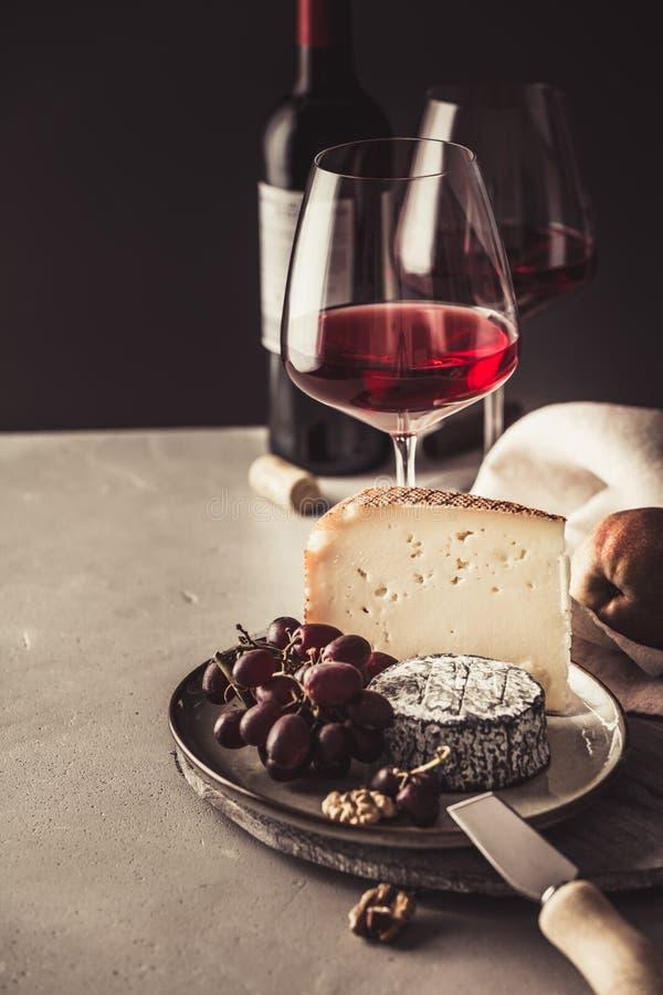 Placa do vinho tinto e de queijo com frutos e porcas imagem de stock