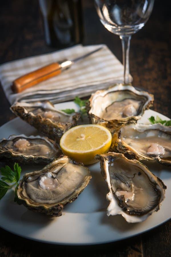 Placa e limão frescos do branco de ostras na mesa de madeira foto de stock royalty free
