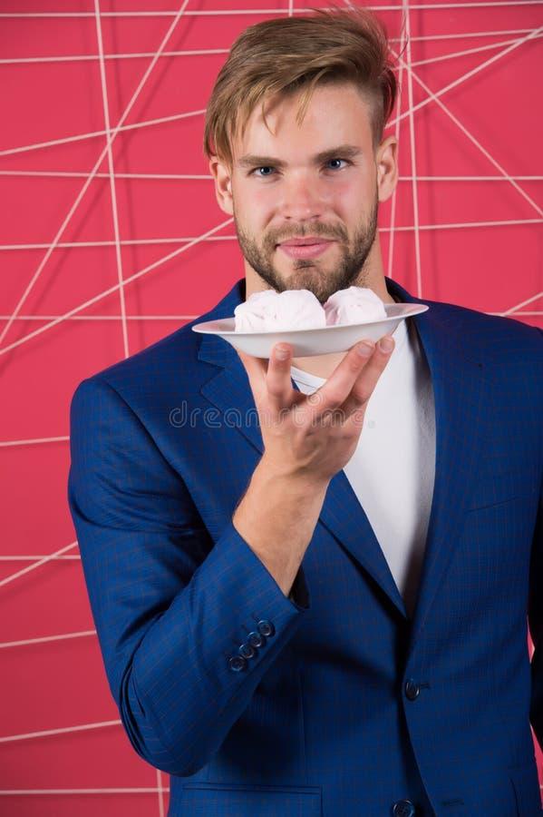 Placa elegante formal da posse do terno do homem com a sobremesa doce do marshmallow Deleites elegantes do doce da oferta do indi fotos de stock