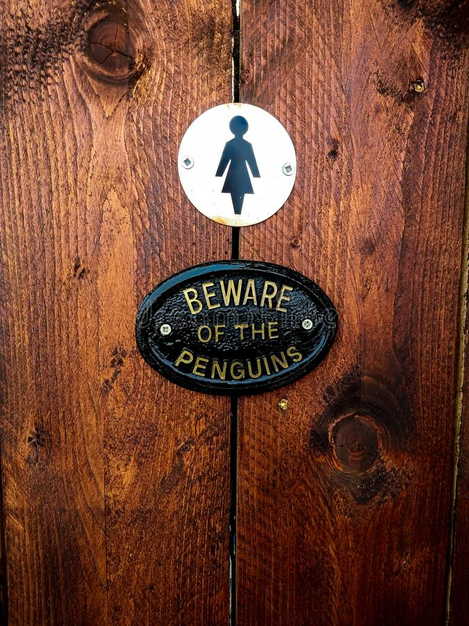 Placa em pinguins fêmeas do banheiro foto de stock
