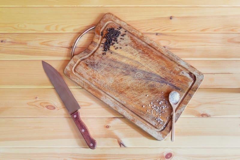Placa, faca e temperos de corte no fundo de madeira Vista superior, espa?o da c?pia imagens de stock royalty free