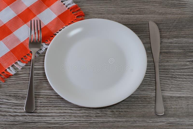 Placa, faca, forquilha e toalha de mesa redondas brancas vazias em t de madeira fotografia de stock
