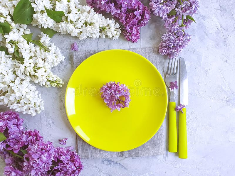 Placa, flor de la lila en la celebración festiva elegante del diseño del vintage de la primavera un fondo concreto gris fotos de archivo