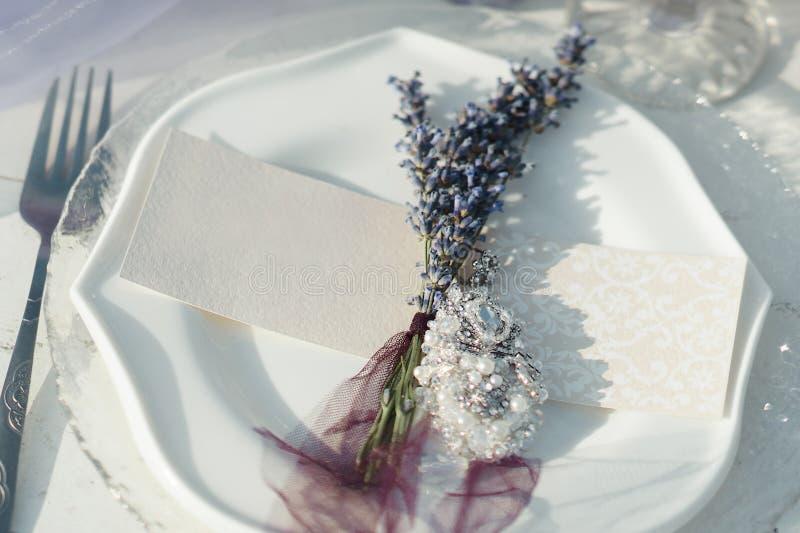 Placa, forquilha, cartão do convidado e boutonniere brancos da alfazema foto de stock