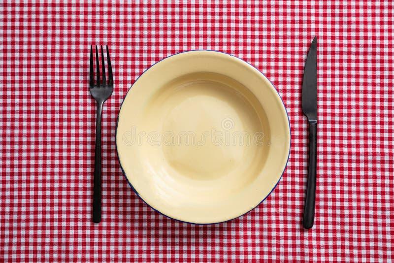 Placa, forquilha e faca vazias do esmalte na toalha de mesa quadriculado vermelha, vista superior fotografia de stock