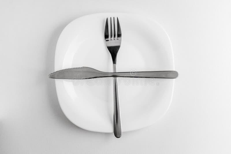 a placa, a forquilha e a faca vazias encontram-se transversalmente em um fundo branco fotografia de stock