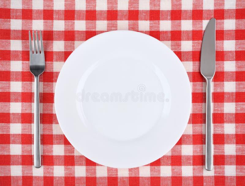 Placa, forquilha, faca em uma toalha de mesa quadriculado vermelha imagens de stock