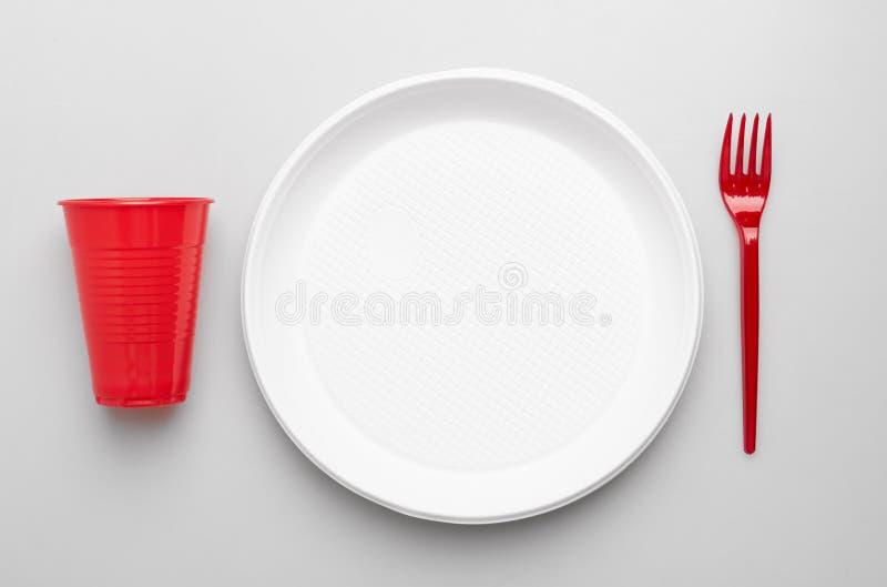 Placa, forquilhas e copo plásticos no branco imagens de stock royalty free