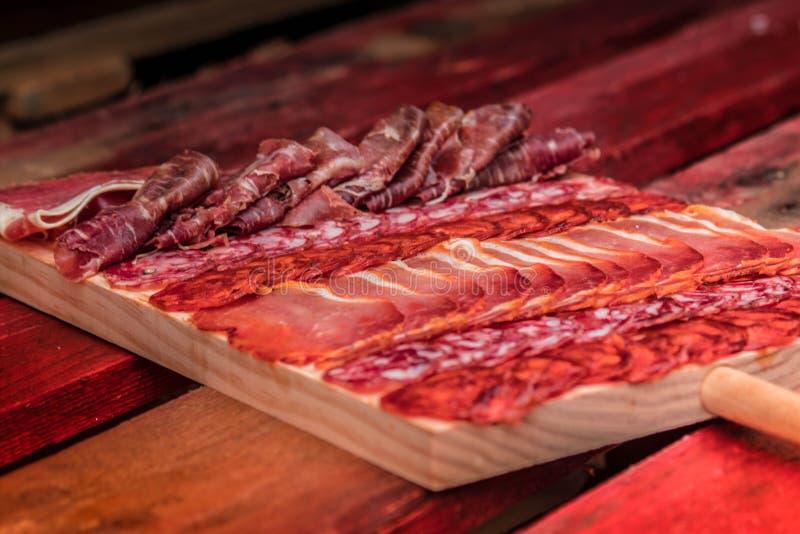 Placa gastrónoma del jamon del jamón del serrano y salchicha en España Placa de madera fotografía de archivo