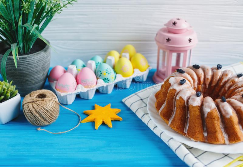 Placa grande com bolo e os ovos coloridos pintados à mão, na toalha no fundo azul Fim acima Decoração para Easter, imagens de stock royalty free