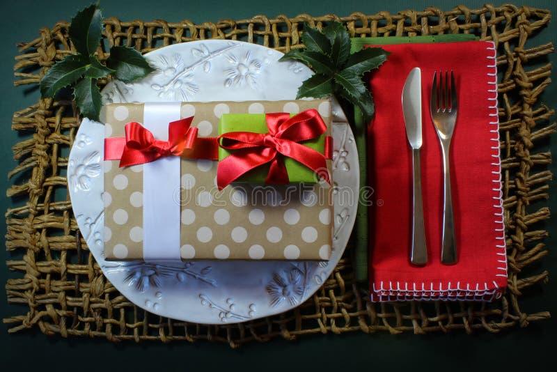 Placa hecha a mano blanca con los regalos de la Navidad y el cubierto de la cena del día de fiesta del acebo imagen de archivo