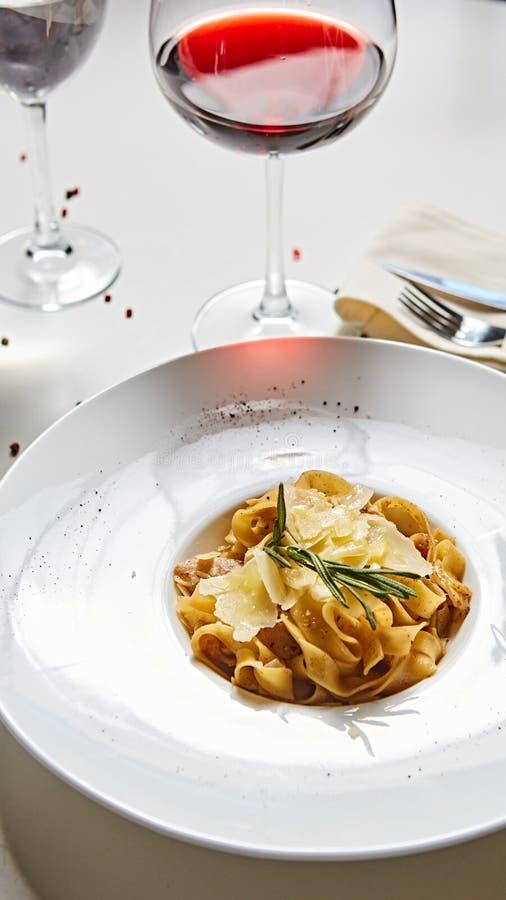 Placa italiana da massa do close-up com queijo parmesão e a folha raspados da manjericão fotos de stock