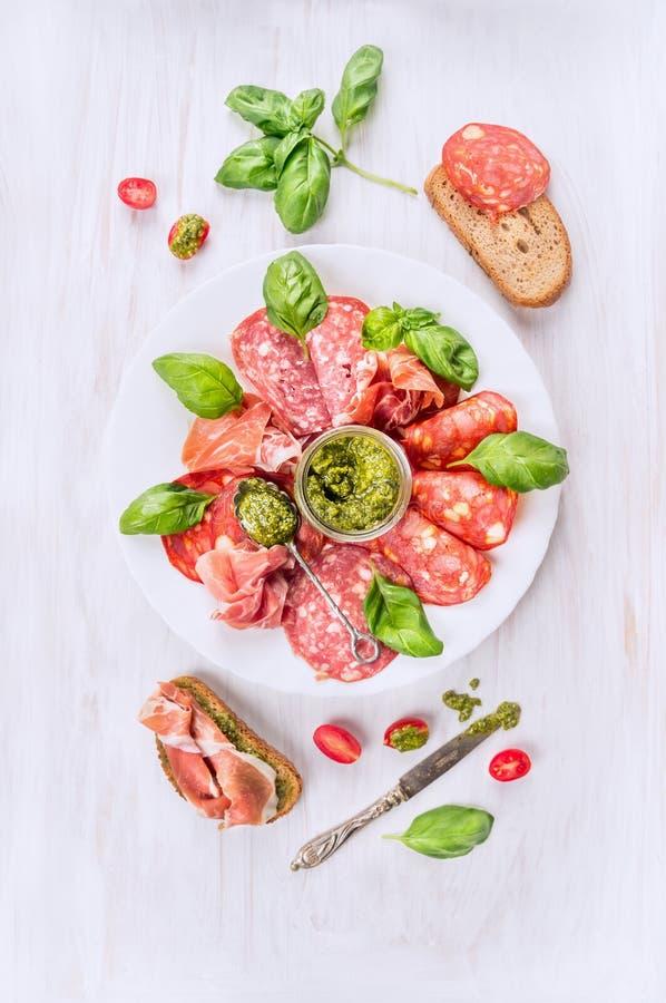 Placa italiana de la carne fría con pan, pesto de la albahaca y tomates fotos de archivo