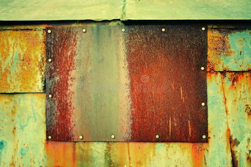 placa marrom oxidada do ferro aparafusado a uma parede azul oxidada do metal fotos de stock