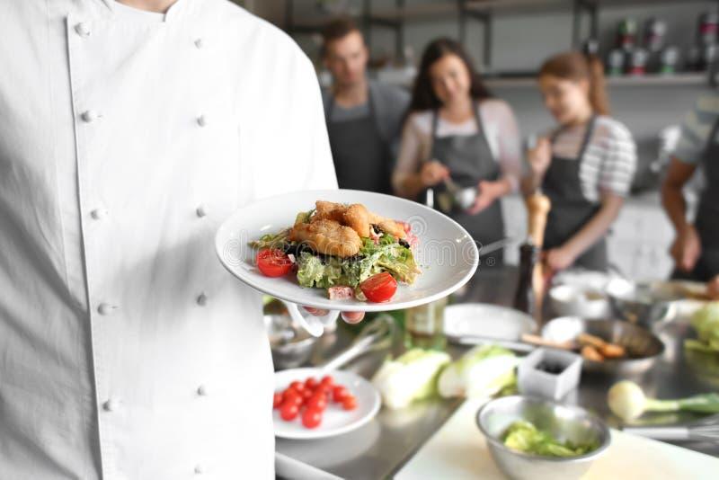 Placa masculina da terra arrendada do cozinheiro chefe com o prato preparado durante aulas de culinária foto de stock