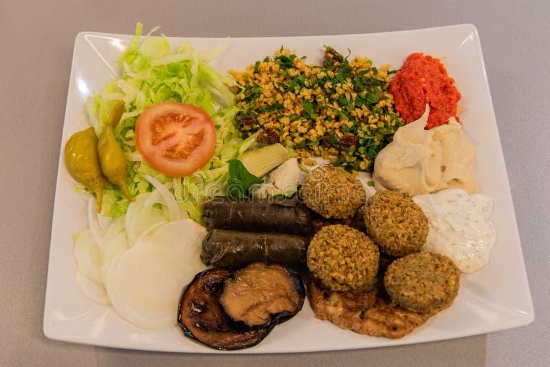 Placa medio-oriental con el bulgur, ensalada, falafel, dolma de la hoja de la vid, berenjena asada a la parrilla, hummus imagen de archivo libre de regalías