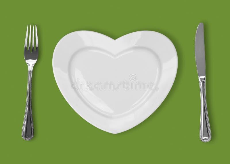Placa na forma do coração, da faca de tabela e da forquilha no backgroun verde ilustração royalty free