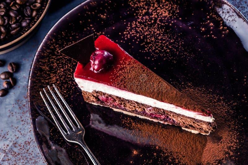 Placa negra con la torta de chocolate deliciosa en fondo gris imágenes de archivo libres de regalías