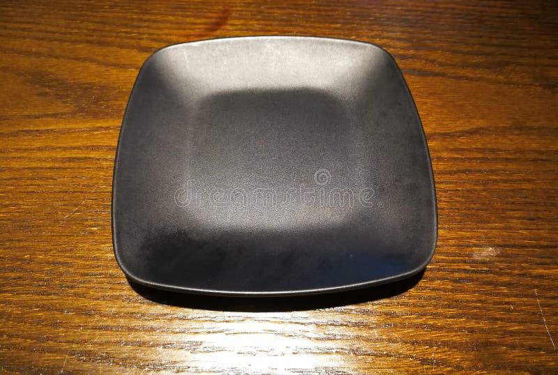 Placa negra vacía en la tabla imágenes de archivo libres de regalías