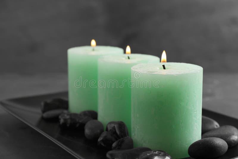 Placa oscura con tres velas y rocas ardientes foto de archivo