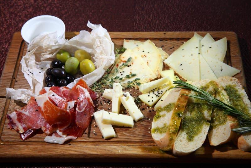 Placa para um bom humor Vitela e jamon emendado secado, queijos crafted e azeitonas imagens de stock