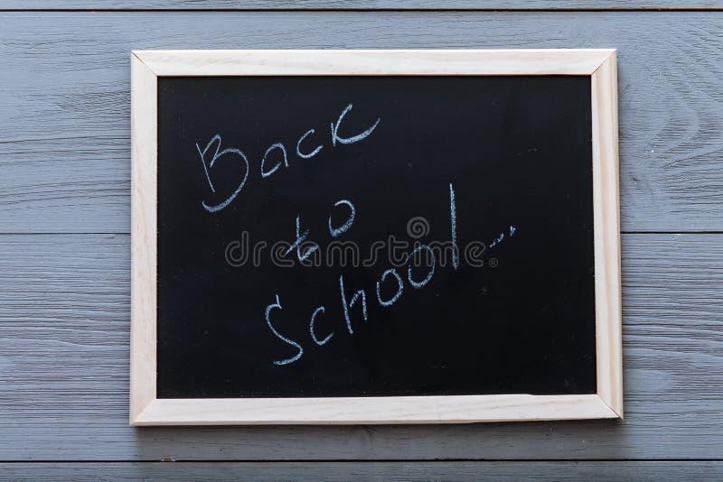 Placa preta com de volta à inscrição da escola escrita no quadro e no giz no fundo de madeira cinzento, começando ano escolar nov fotos de stock royalty free