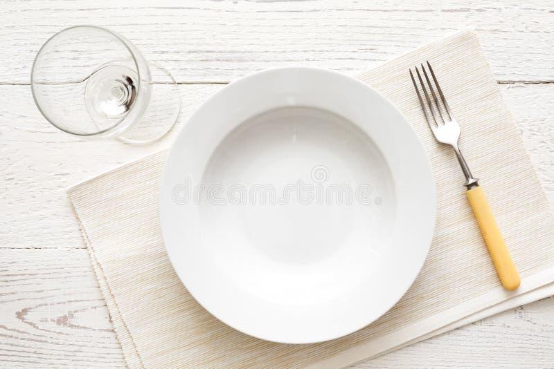 Placa redonda branca vazia da sopa ou da massa com forquilha e vidro no wh imagens de stock