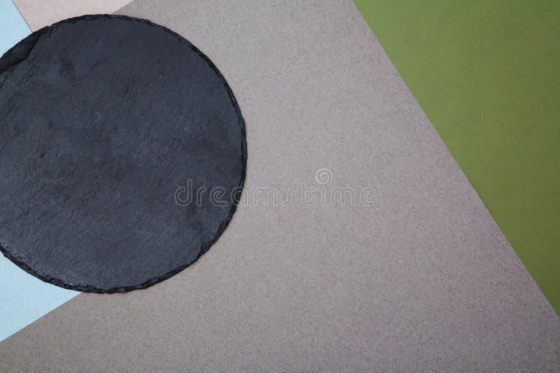 Placa redonda da ardósia arranjada no fundo colorido simples com papéis cinzentos e azuis e verdes fotografia de stock royalty free