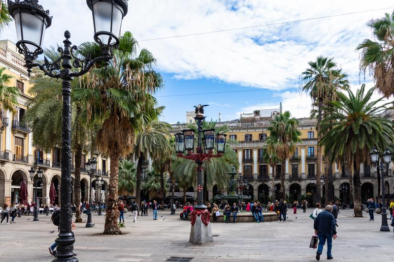 Placa Reial, shaded by palms and cooled by a fountain. Colorful lamp posts known as Gaudì first opera in the center. Barcelona stock photo