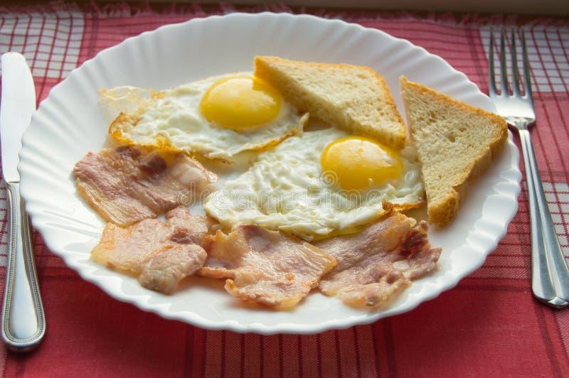 Placa saboroso do café da manhã dos ovos fritos, bacon e brinde, ao lado da cutelaria no guardanapo quadriculado vermelho fotografia de stock royalty free