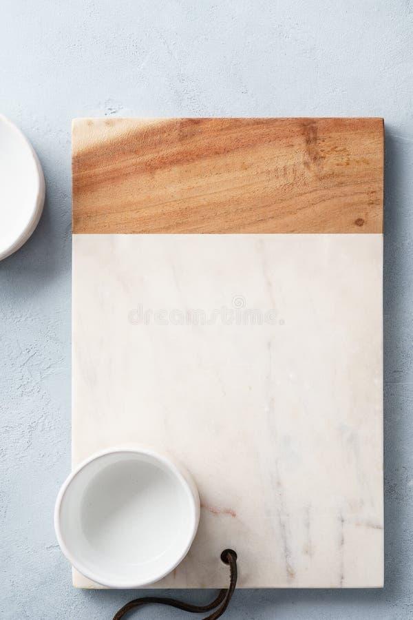 Placa servindo de mármore e de madeira retangular e uma bacia fotografia de stock