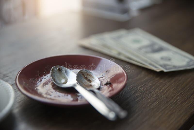 Placa suja da placa vazia com o bolo após comer com dinheiro do dólar, lugar na tabela de madeira na cafetaria Verifique a conta  fotos de stock