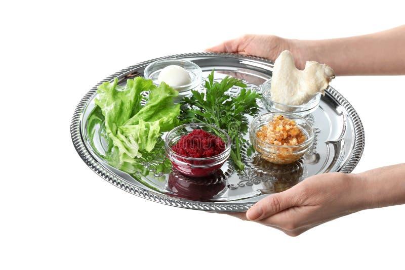 Placa tradicional de la placa de Pesach Seder de la pascua judía de la tenencia de la mujer con la comida simbólica en el fondo b imágenes de archivo libres de regalías