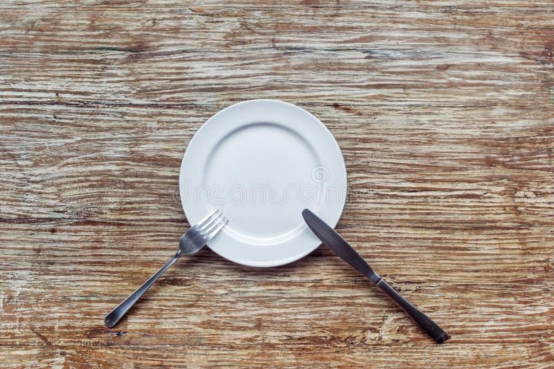 Placa vacía blanca en la tabla de madera fotos de archivo