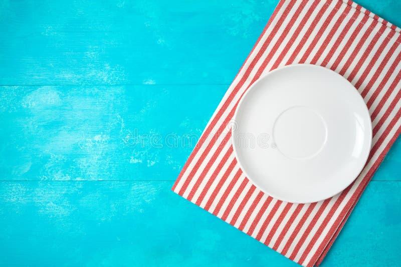 Placa vacía blanca y mantel rayado rojo en fondo de madera azul Visi?n superior desde arriba foto de archivo libre de regalías