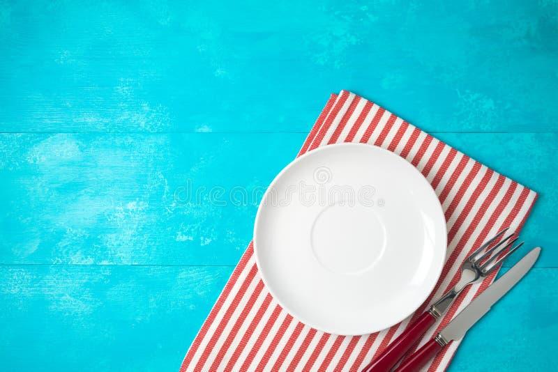 Placa vacía blanca y mantel rayado rojo en fondo de madera azul Visi?n superior desde arriba fotografía de archivo