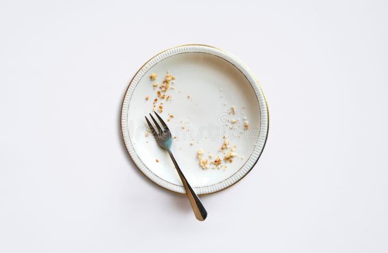 Placa vacía con las migas después de comer en un fondo blanco T foto de archivo