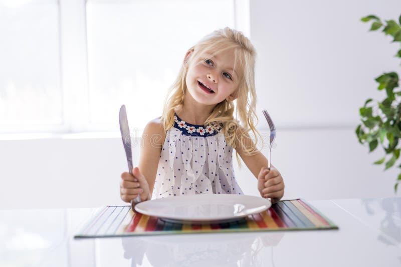 Placa vacía de la bifurcación de la tenencia de la niña lista para la comida imagenes de archivo