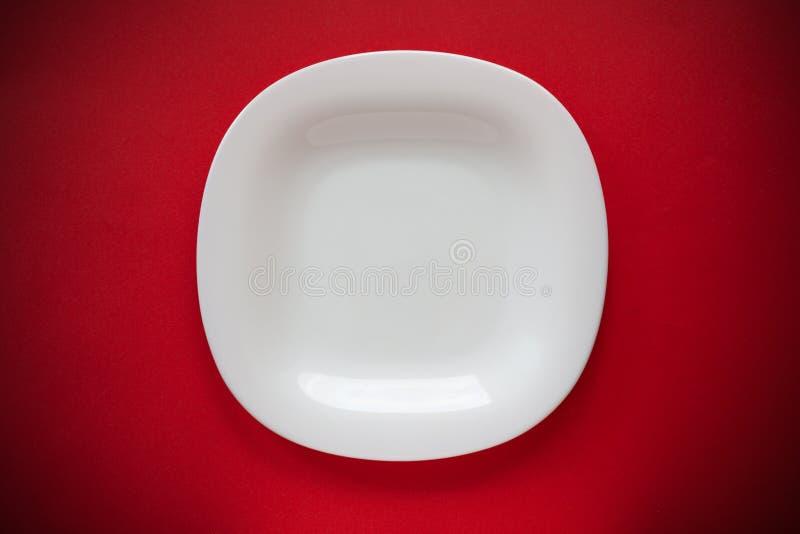 Placa vazia branca em um fundo vermelho com configuração lisa da opinião superior do vignetting imagens de stock royalty free