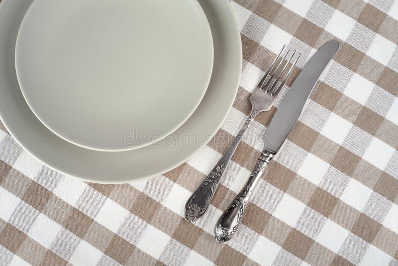 Placa vazia cinzenta com forquilha do vintage e faca na toalha de mesa quadriculado bege foto de stock royalty free