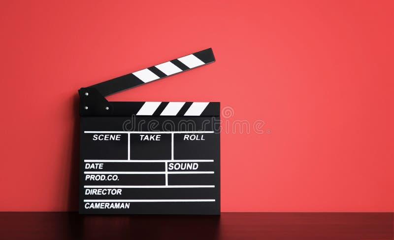 Placa vazia do cinema da válvula da placa ou do filme de válvula do filme, filme da ardósia em de madeira preto com fundo vermelh fotografia de stock royalty free