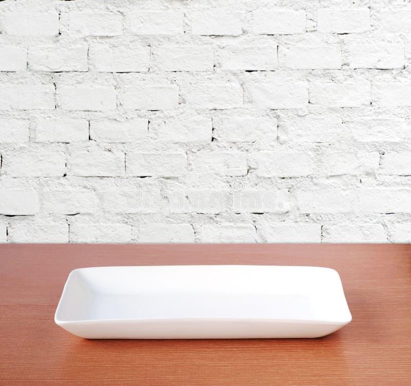 Placa vazia na tabela de madeira sobre o fundo branco da parede de tijolo, alimento fotos de stock