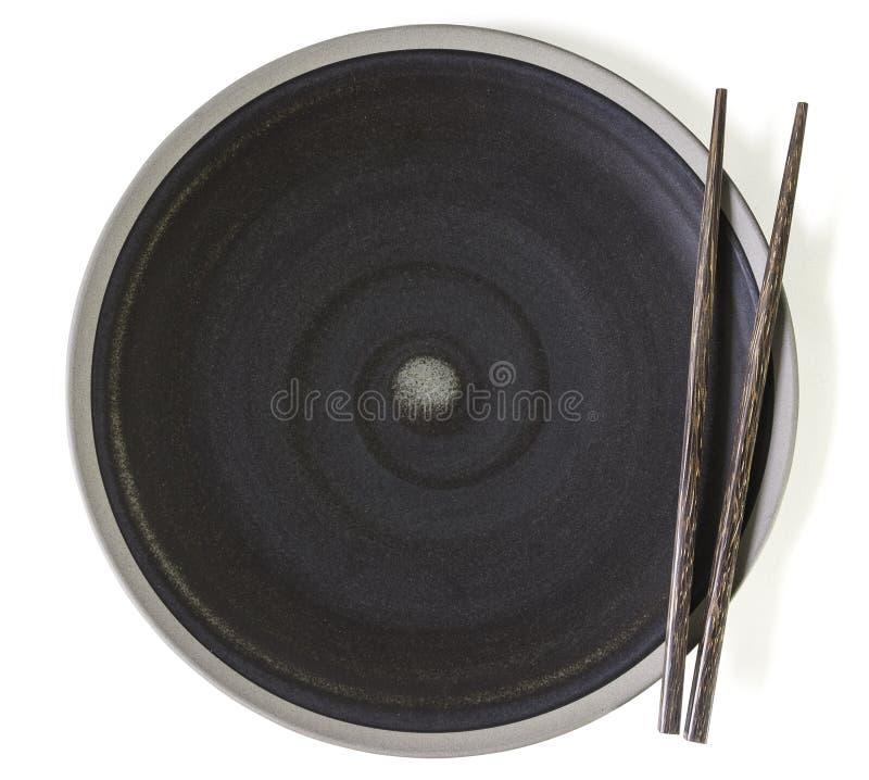 Placa vazia preta com os hashis pretos de madeira no fundo branco foto de stock royalty free