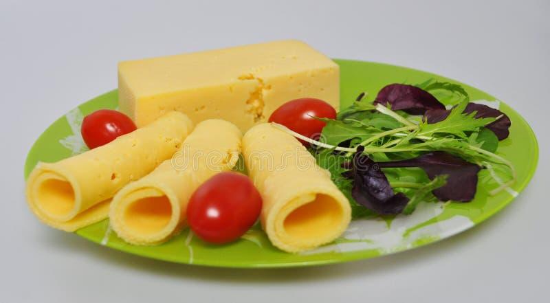 Placa verde con la comida - queso, tomates, lechuga foto de archivo